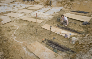 An archaeologist excavates a casket lid from the Mississippi State Asylum (image from University of Mississippi Medical Center Public Affairs)